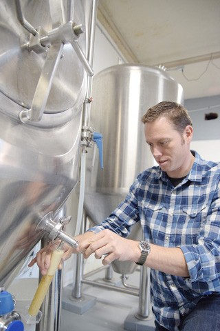 Brewmaster Stephen Basey draws some beer for testing at Lazy Circles Brewing. (Photo Mark Hancock)