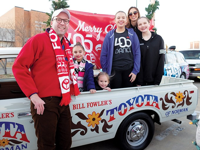 Jonathan Fowler poses with a restored 1973 Toyota pickup at the Norman Christmas Parade. The pickup was restored with the same body paint used on one that was driven in the parade in the 1970s. - FOWLER HOLDING COMPANY / PROVIDED