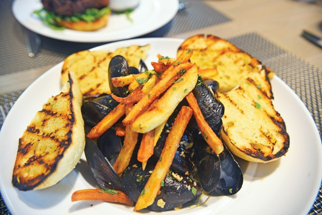 Moules-frites are mussels and french fries in a - white wine garlic broth - JACOB THREADGILL
