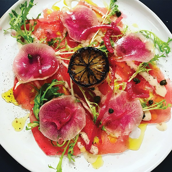 Tuna carpaccio with yellow fin tuna, capers, pickled onions, frisée, breakfast radish and burnt lemon vinaigrette. - PROVIDED