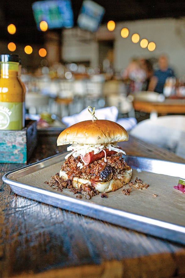 The Full Boar sandwich is piled high with pulled pork, brisket, a hot link and coleslaw. - ALEXA ACE