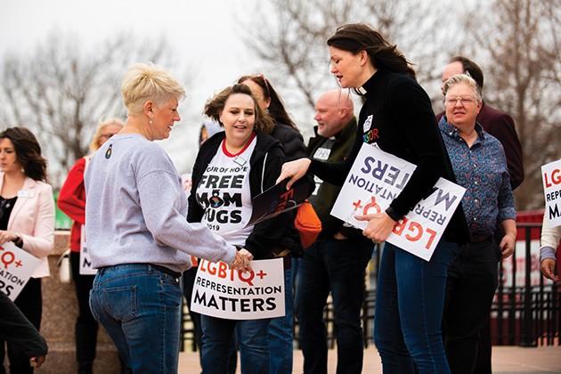 "Rev. Lori Walke hands Sara Cunningham, founder of Free Mom Hugs, an ""LGBTQ+ Representation Matters"" sign. - MIGUEL RIOS"