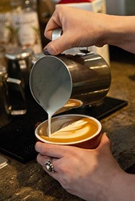 steamed milk is poured in the making of a latte by barista Tori Goben, at Coffee Slingers Roasters.  mh