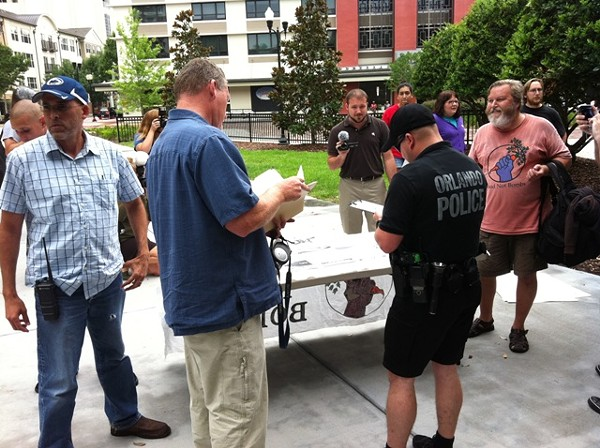 A mix of undercover and uniformed police officers serve a revised trespassing warrant to Food Not Bombs co-founder, Keith McHenry, at right.