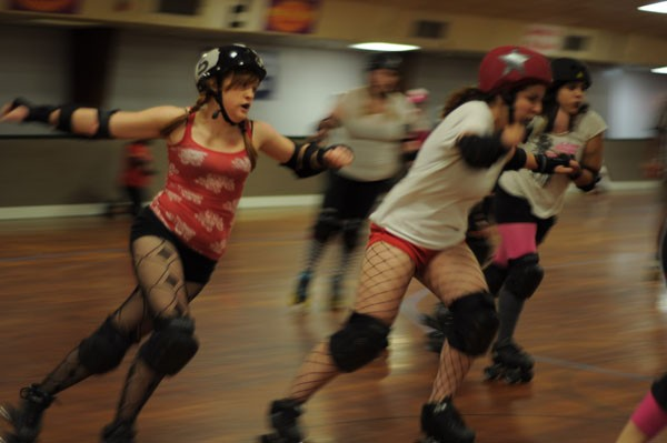 Playing nice: The Bellevue Bombshell jammer known as 'Ellen Rage' passes by Serial Thriller player 'Knock'em Over Clover' during a practice bout in October. - J. HUNTER SIZEMORE