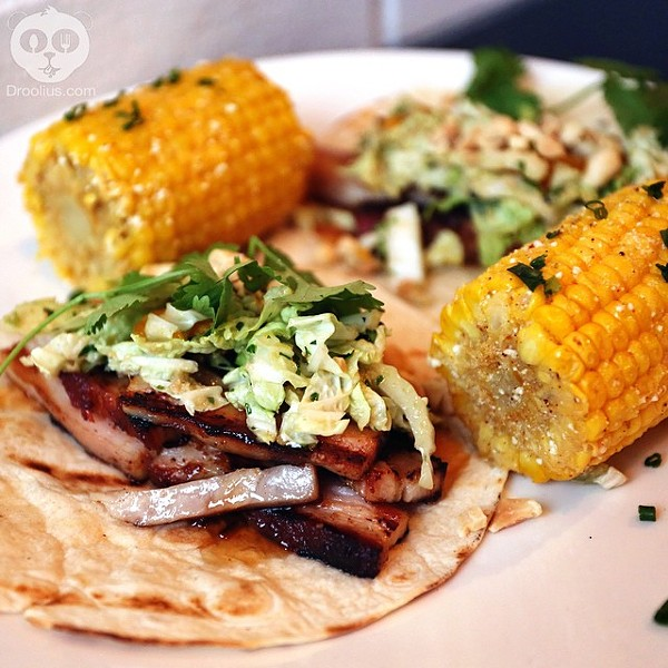 Pork belly tacos and a side of grilled corn on the cob with chili & lime