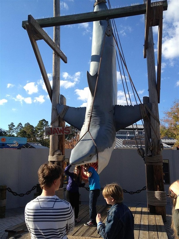 Tourists pose in front of Universal's shuttered Jaws ride.