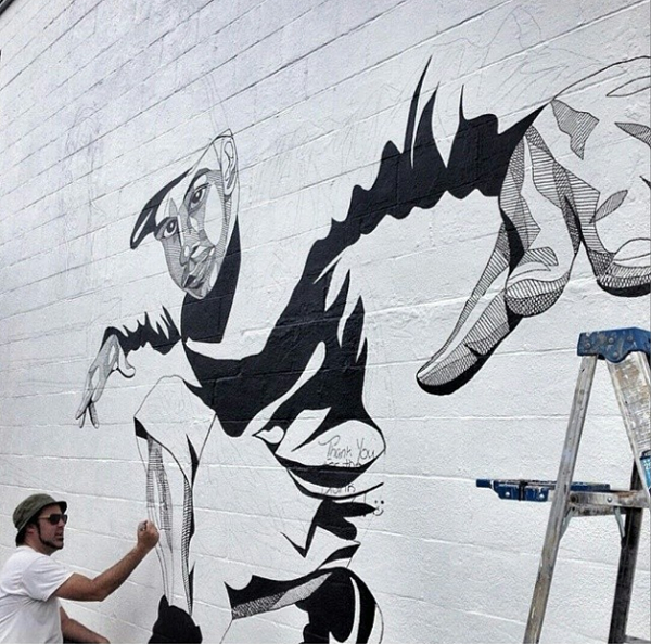 ANDREW SPEAR WORKING ON A MILLS 50 MURAL