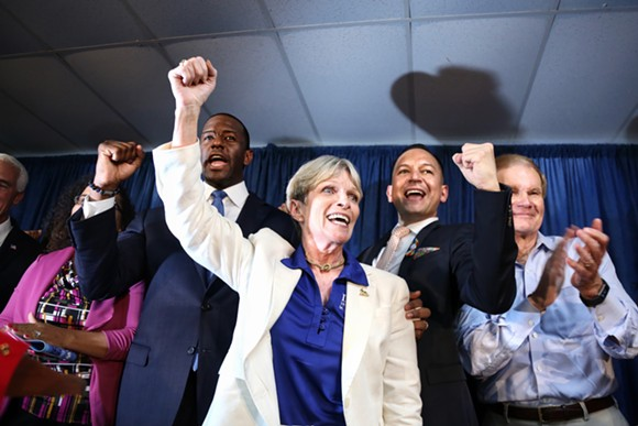 """Florida Democratic Party chairwoman Terrie Rizzo chants """"Bring it home!"""" with gubernatorial nominee Andrew Gillum (left), State Rep. Carlos Smith, and U.S. Sen. Bill Nelson (far right) to conclude a Democratic victory rally in Orlando on Aug 31 2018. - PHOTO BY JOEY ROULETTE"""