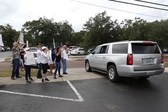 Demonstrators protest Ricardo Rosselló as his motorcade leaves for an Andrew Gillum event in Kissimmee on Monday. - PHOTO BY JOEY ROULETTE