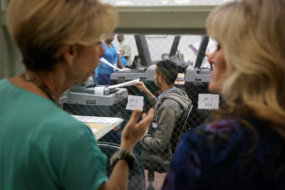 Onlookers watch rows of poll staffers tackle the first wave of recount ballots inside an Orange County Supervisor of Elections warehouse on Nov. 12 2018. - PHOTO BY JOEY ROULETTE