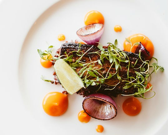 Pork belly adobo with black rice and calamansi lime. - PHOTO BY HANNAH GLOGOWER
