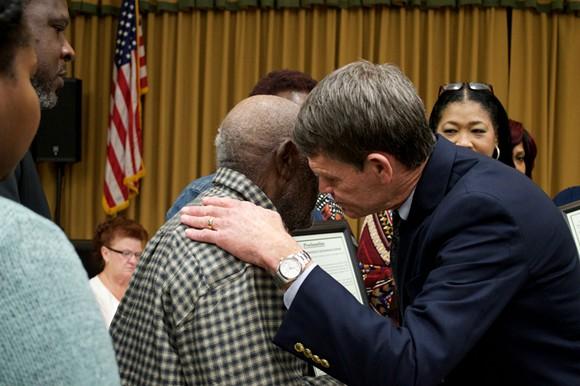 Groveland Mayor Tim Loucks hugs a relative of the Groveland Four. - PHOTO BY MONIVETTE CORDEIRO
