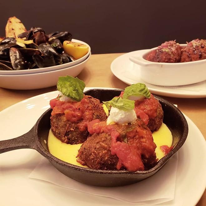 Arancini (fried risotto balls) with gorgonzola, fig, prosciutto and pesto cream sauce. - HOLLY V. KAPHERR