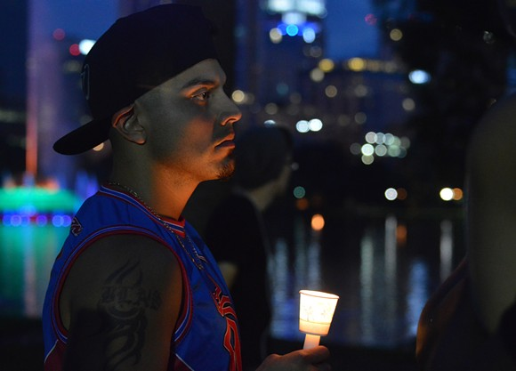 A man holds a candle at vigil in Lake Eola after the mass shooting at Orlando's Pulse nightclub. - PHOTO BY MONIVETTE CORDEIRO