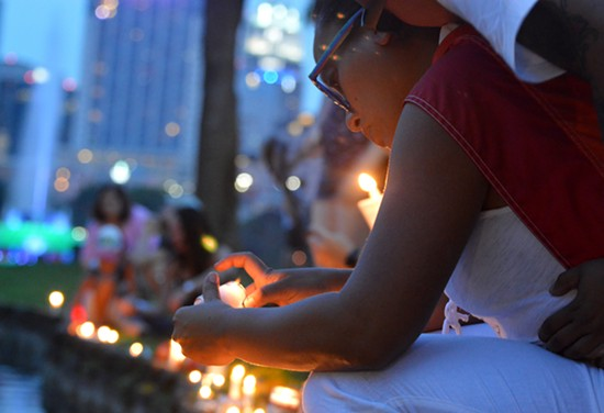 A woman lights a candle at a small vigil for victims of the mass shooting at Pulse nightclub in Orlando. - PHOTO BY MONIVETTE CORDEIRO