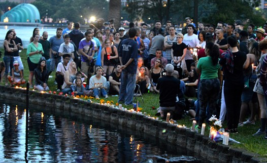 People lay candles at a small vigil for victims of the mass shooting at Pulse nightclub in Orlando. - PHOTO BY MONIVETTE CORDEIRO