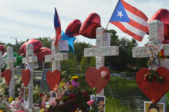 Puerto Rican flags fly over the cross memorial installed near Orlando Regional Medical Center. - PHOTO BY MONIVETTE CORDEIRO