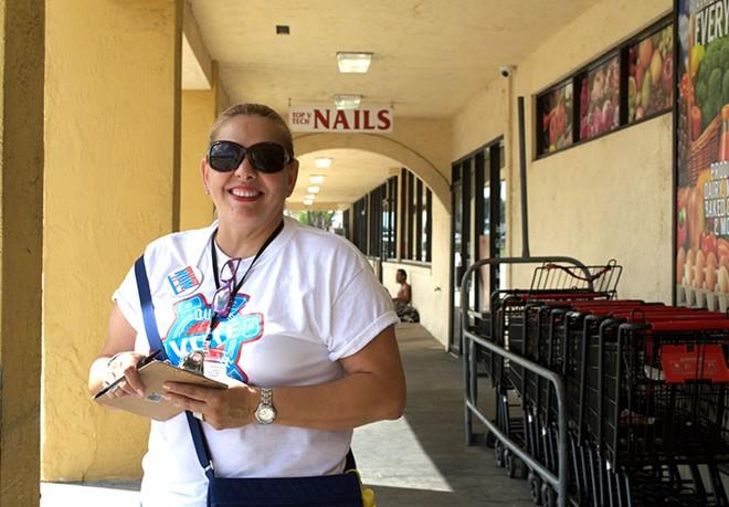 Maria Merced Valiente waits at Bravo Supermarket to register voters. - PHOTO BY MONIVETTE CORDEIRO
