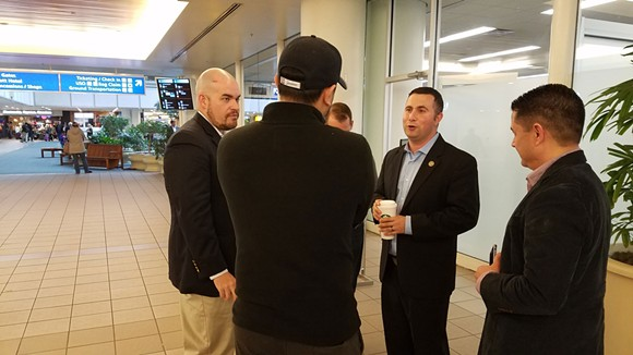1:31 p.m.: Alex Barrio, Rep. Darren Soto, and Henry Lim talk with a friend of one of the travelers. - DAVE PLOTKIN