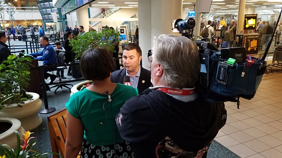 1:55 p.m.: Rep. Soto speaks to television news crews, sharing information about the travelers from airport and federal officials. - DAVE PLOTKIN
