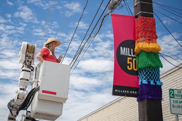 "Victoria Walsh, also known as ""Macrame Momma,"" installing a work in Mills 50 - IMAGE VIA VICTORIA WALSH / FACEBOOK"