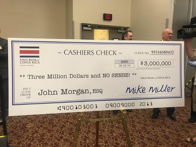 The Tiger Bay Club in Tallahassee displayed for Morgan a giant, fake check to poke fun at an ethics probe that included allegations about Gillum traveling to Costa Rica with an undercover FBI agent, who posed as Mike Miller. - PHOTO COURTESY NEWS SERVICE OF FLORIDA