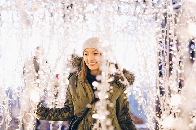 enchant-christmas-hanging-lights-young-woman-1000.jpg