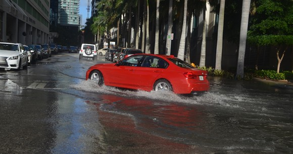 A car drives through flooded streets in Miami - PHOTO VIA B137/WIKIMEDIA COMMONS