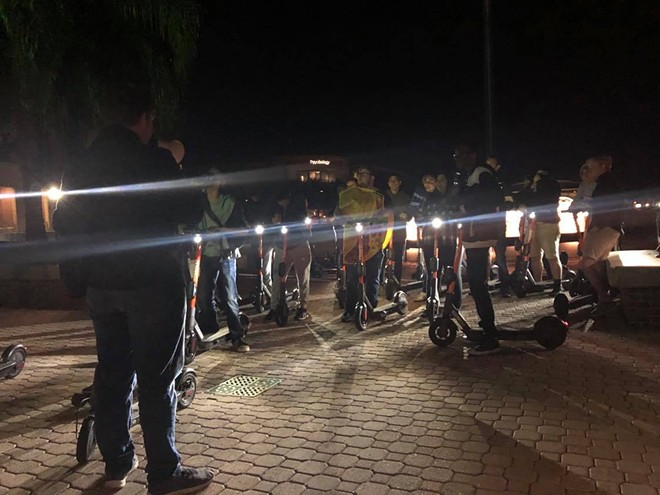 """Dozens of UCF students gather every Friday night at 9 p.m. to ride around campus as """"Spin Squad,"""" a social group that formed recently due to the new scooters on campus. - LILLIAN M. HERNÁNDEZ CARABALLO"""