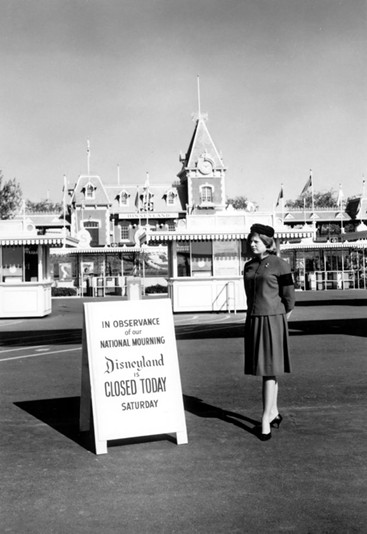 A cast member stands by a sign informing guests the Disneyland park is closed for the National Day of Mourning following President Kennedy's assassination - IMAGE VIA DISNEY/DISNEY.COM