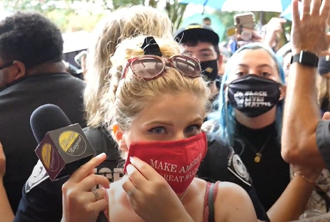 Conservative gun rights activist Kaitlin Bennett puts on her MAGA face covering outside the John C. Hitt library, as per UCF's new COVID-19 policies and UCF PD directives. It took students, staff, and police nearly two hours to get her to comply. - LIBERTY HANGOUT