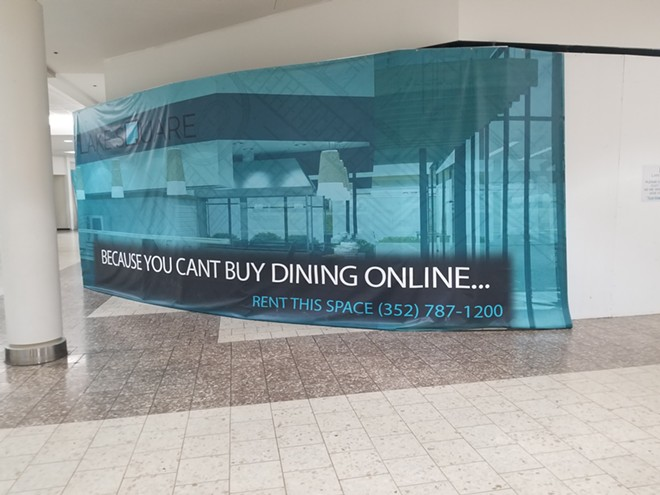 A sign hiding an empty storefront inside the Lake Square Mall - IMAGE VIA KEN STOREY