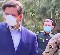 Florida Governor and anti-science champion Ron DeSantis seemingly struggling to understand how to properly wear a mask. - SCREENSHOT VIA @THEWESTIPHER/TWITTER