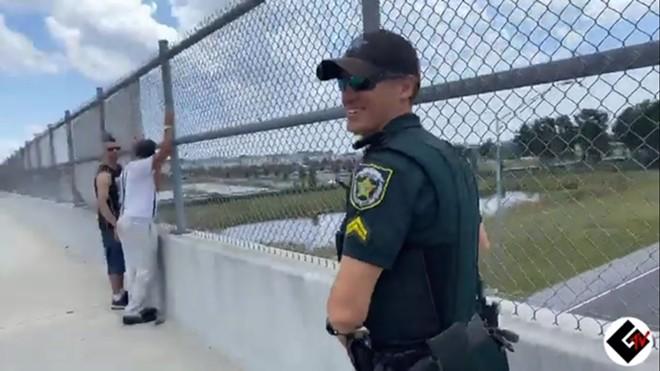 An Orange County Sheriff's Office deputy smiles while handing water to neo-Nazis. - SCREENSHOT VIA TWITTER/ST PETE COP WATCH