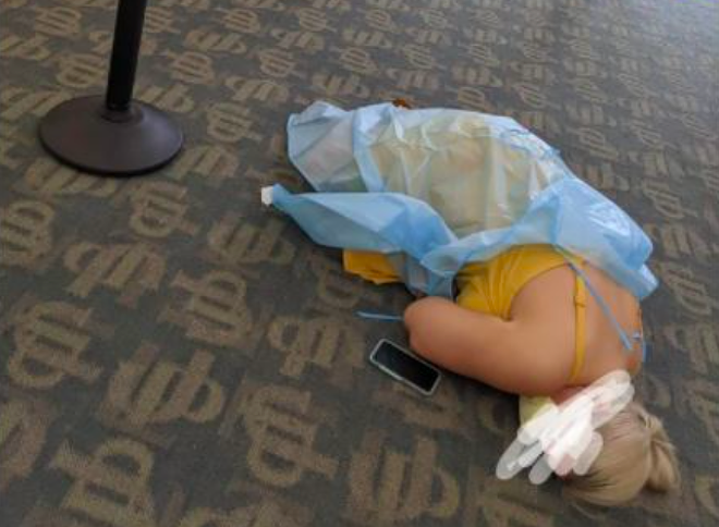 A photo of a woman lying on the floor while waiting for COVID-19 antibody treatment has gone viral. - PHOTO VIA REDDIT