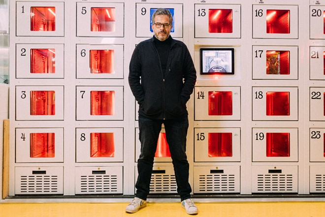 Founder Stratis Morfogen in front of a wall of heated lockers at Brooklyn Dumpling Shop. - PHOTO COURTESY OF BROOKLYN DUMPLING SHOP