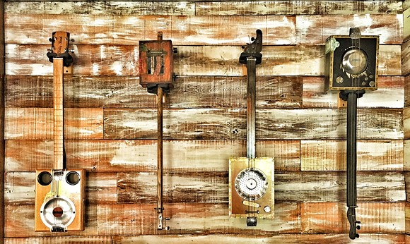 More art inside the restaurant: functional cigar-box guitars, made by local artist Kyle Wenzel - PHOTO VIA BEACON HILL GROUP