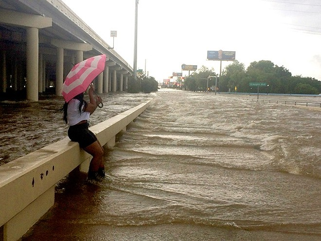 An umbrella didn't furnish a lot of protection Sunday morning at Yale and Interstate 10. - PHOTO BY MEAGAN FLYNN
