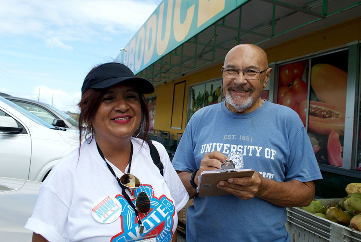 A canvasser for Que Vote Mi Gente registers a man to vote by mail.