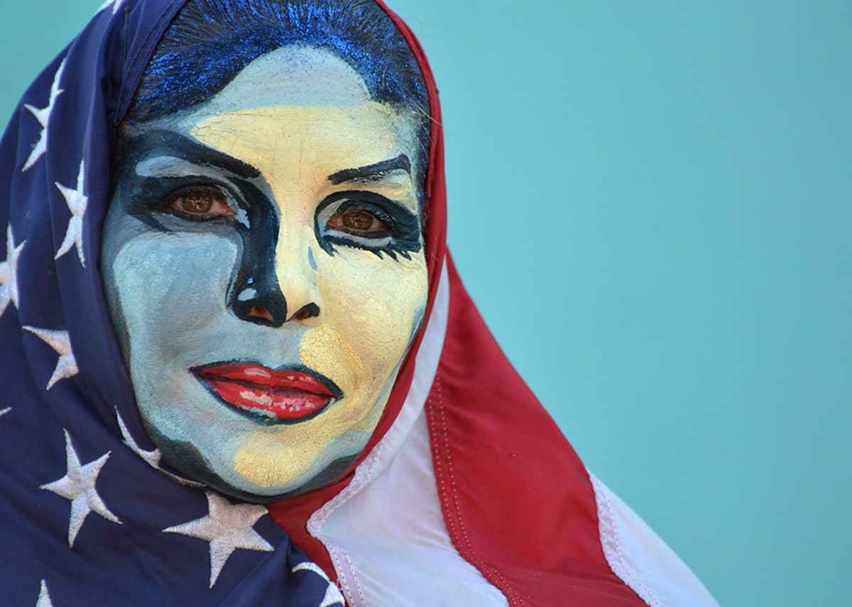 "Model Jill Miller emulates the ""We the People"" artwork of Shepard Fairey, painted on her by body painting artist Shannon Holt"