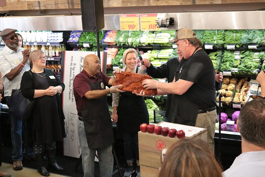 David Maloo (Assistant Store Director), Trish and Bo Sharon (owners), and Bob Knaus  (Store Director) cut house-cured bacon instead of a ribbon to celebrate the opening of Lucky's Market - PHOTO COURTESY LUCKY'S MARKET