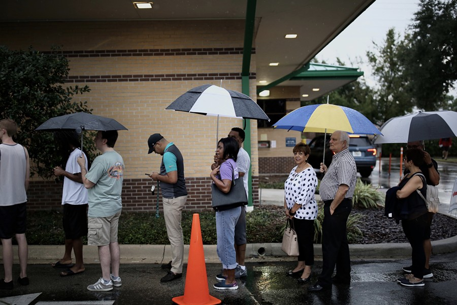 Voters stand in the rain in line to vote at the Alafaya Branch Library precinct on Nov. 6 2018, the highest general election day turnout since 2012. - PHOTO BY JOEY ROULETTE