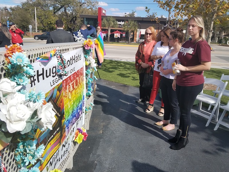 Natasha McImurray and her co-workers stand in front of the Pulse Interim Memorial. - ELIZABETH GONDAR
