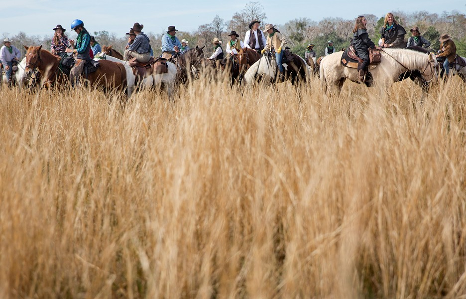 Riders rest their horses in the tall grasses at the end of the trail.