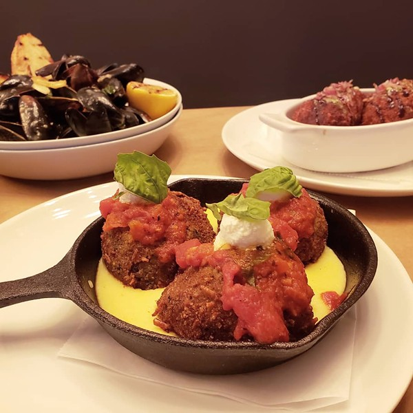 Arancini (fried risotto balls) with gorgonzola, fig, prosciutto and pesto cream sauce. - HOLLY V. KAPHERR