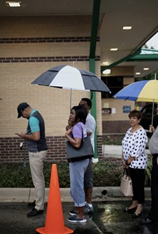 Voters stand in the rain in line to vote at the Alafaya Branch Library precinct on Nov. 6 2018, the highest general election day turnout since 2012.