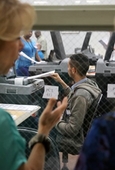 Onlookers watch rows of poll staffers tackle the first wave of recount ballots inside an Orange County Supervisor of Elections warehouse on Nov. 12 2018.