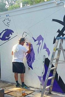 Artist Andrew Spear working on the new Prince mural at Hideaway Bar