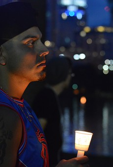 A man holds a candle at vigil in Lake Eola after the mass shooting at Orlando's Pulse nightclub.